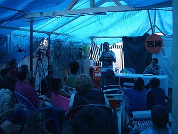 Miguel Presno de pie con el micro en la carpa de la Asamblea 15-M