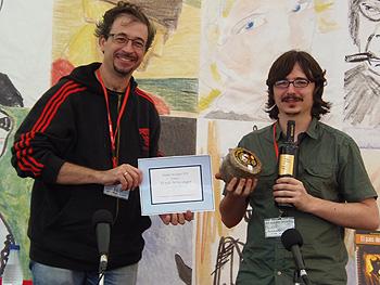 José Luis Gómez de Novelpol entrega el diploma de ganador a Claudio Cerdán que muestra el queso y el vino